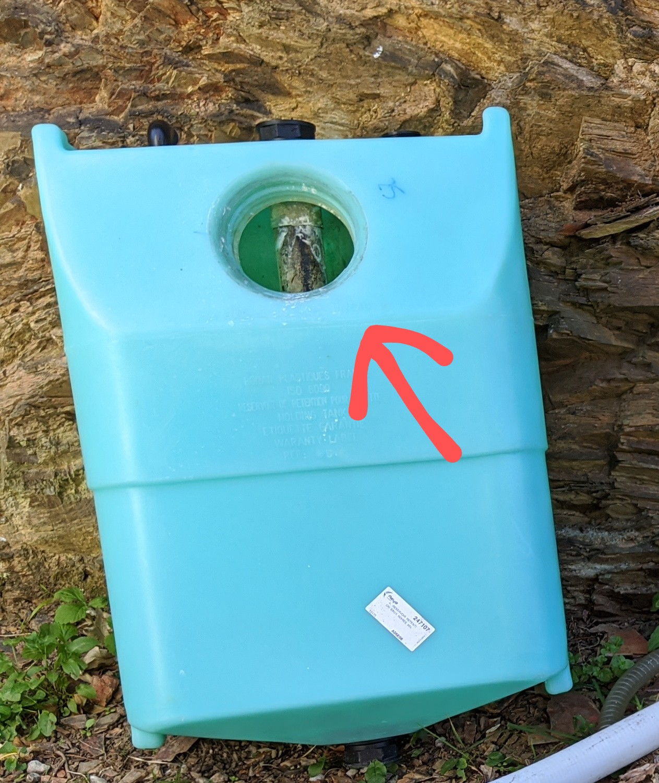 Couvercle de la trappe de visite d'un réservoir d'eau noir.